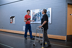 A physiotherapist with a patient using a walker